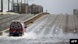 An ambulance drives on a flooded street in the aftermath of Hurricane Maria in San Juan, Puerto Rico, Sept. 22, 2017.