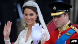 Britain's Prince William and his wife Kate, Duchess of Cambridge, wave as they travel in the 1902 State Landau carriage along the Processional Route to Buckingham Palace, in London, April 29, 2011.