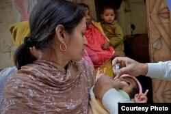 ایک بچے کو پولیو سے بچاؤ کی ویکسین کے قطرے پلائے جا رہے ہیں۔ فائل فوٹو