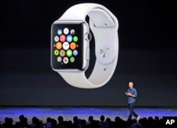 FILE - Apple CEO Tim Cook introduces the new Apple Watch on Tuesday, Sept. 9, 2014, in Cupertino, Calif. Apple's new wearable device marks the company's first major entry in a new product category since the iPad's debut in 2010. (AP Photo/Marcio Jose Sanchez)