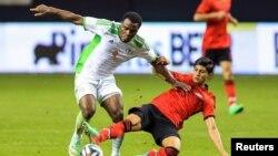 Tiền đạo đội tuyển quốc gia Mexico Alan Pulido (áo đỏ) tranh bóng với Emmanel Emenike của đội Nigeria (áo trắng) trong một trận đấu giao hữu.