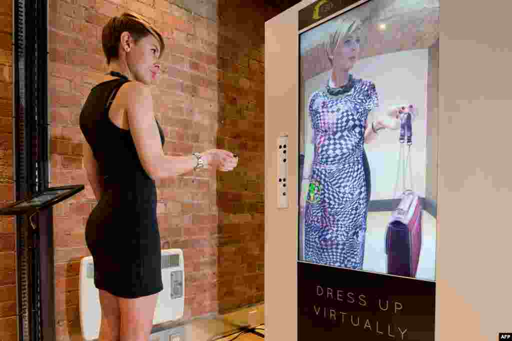 A woman tries out the Virtual Style Pod/Fashion 3D system at the FLux Innovation Lounge in east London. The technology uses body mapping software to superimpose items of clothing onto the customers body so that he or she can try on different styles without having to change clothes. The cameras track the customers movement, allowing them to see how the clothing moves from all sides and angles.