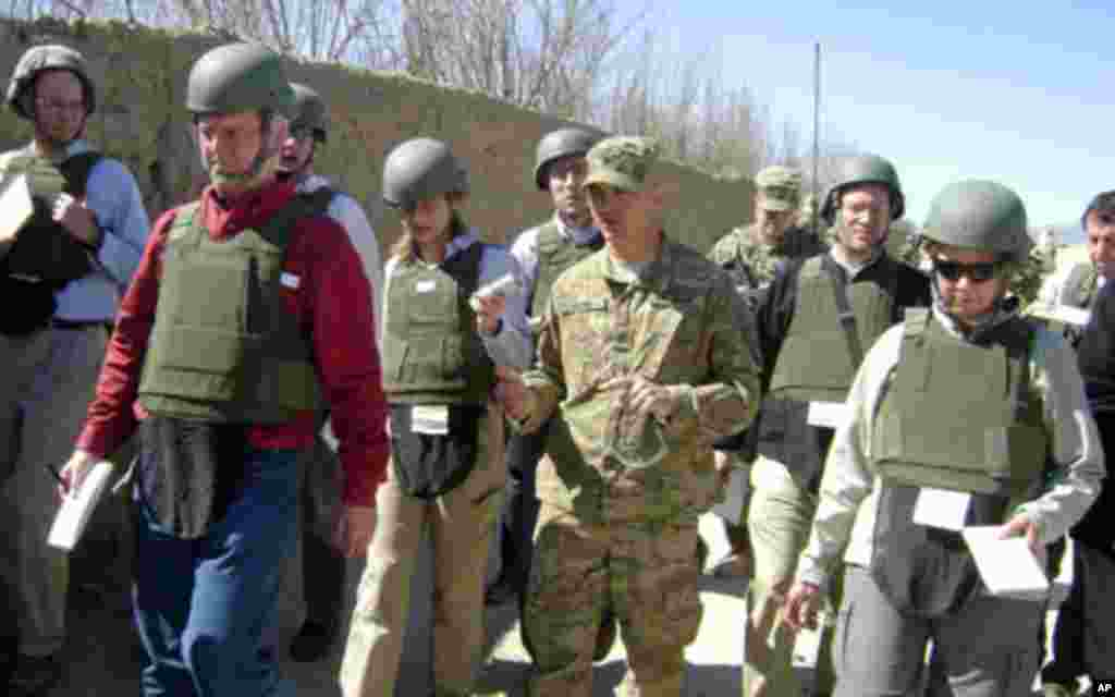 Colonel David Flynn walks toward Tabin Village in Kandahar Province with reporters who are covering Secretary Gates' visit, March 8, 2011