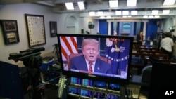 Predsednik Donald Tramp vidi se na ekranima u sobi za brifinge Bele kuće, dok se u udarnom terminu obraća naciji iz Ovalnog kabineta, 8. januara 2019.