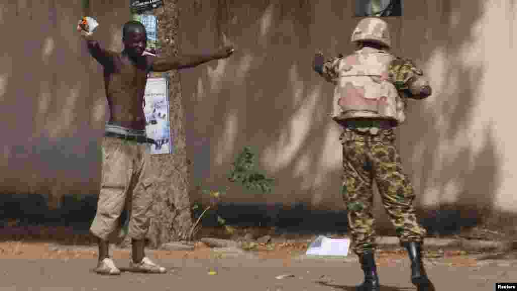 An anti-government protester faces down a soldier outside the parliament building in Ouagadougou, capital of Burkina Faso, Oct. 30, 2014.