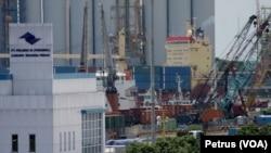Situasi pelabuhan Tanjung Perak Surabaya dengan latar belakang kapal pengangkut kontainer yang akan bersandar (Foto: VOA/Petrus Riski).