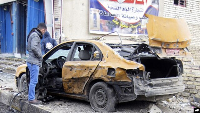 Ahmed Ali inspects his destroyed car after a car bomb explosion in Baghdad, Iraq, February 23, 2012.