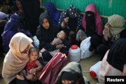 FILE - Rohingya refugee women wait outside of a medical center at Jamtoli camp in Cox's Bazar, Bangladesh, Jan. 22, 2018.