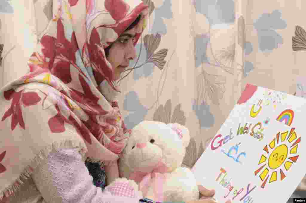 ໃນຮູບທີ່ນໍາອອກເຜີຍແຜ່ໃນວັນທີ 8 ພະຈິກ, 2012, ນາງ Malala Yousafzai ອ່ານບັດອວຍພອນ ໃນຂະນະທີ່ກໍາລັງພັກຟື້ນຢູ່ໂຮງໝໍ ພະລາຊີນີ Elizabeth ໃນເມືອງ Birmingham, ປະເທດອັງກິດ.