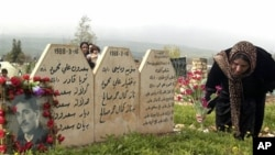 A Kurdish woman places flowers at graves of her loved ones in Halabja, Iraq. (file)