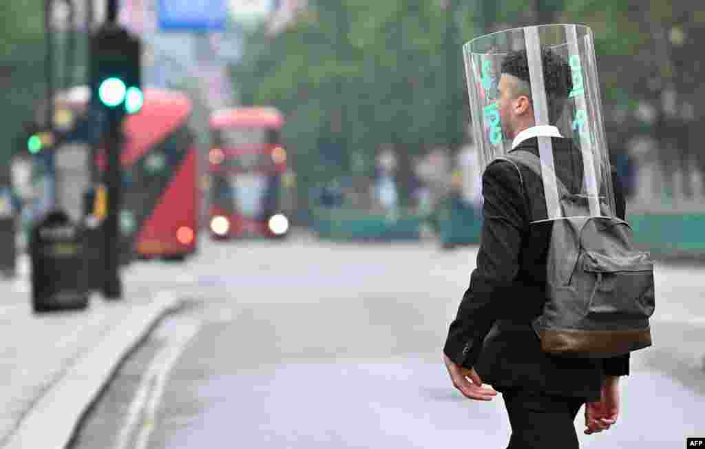 A pedestrian wearing a form of personal protective equipment as a measure to protect against COVID-19 walks across Oxford Street in central London, Britain.