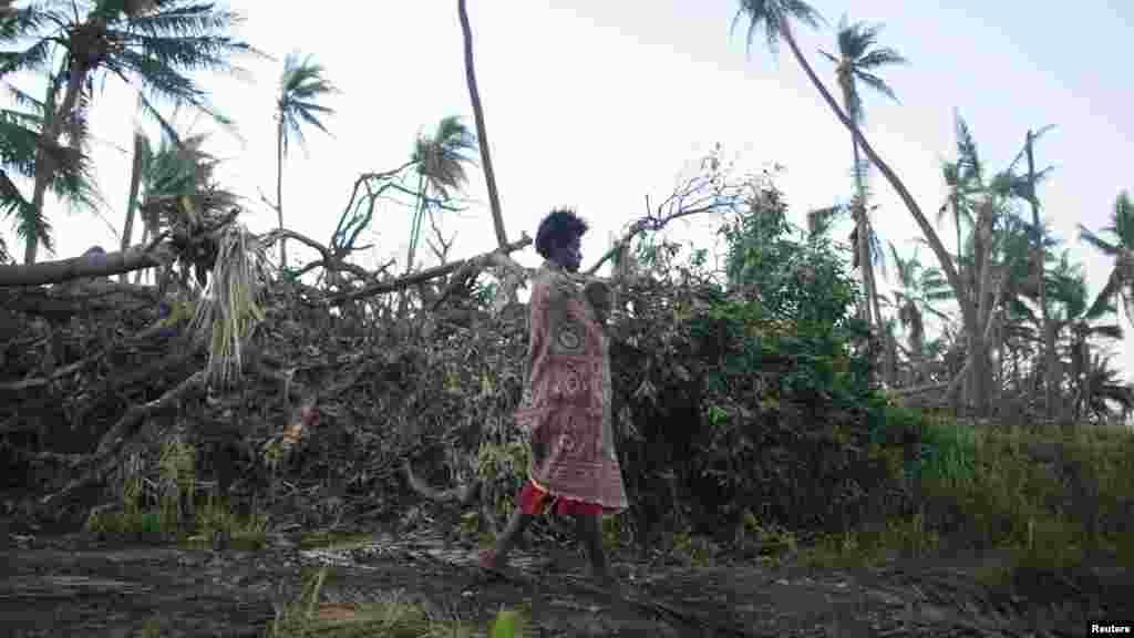 Une dame portant un bébé dépasse des arbres déracinés dans le Sud de l'ile de Tanna, où des habitants affirment être bientôt à court de nourriture puisque l'assistance en denrées alimentaires et biens de première nécessité s'épuisent, le 18 mars 2015.