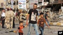 Warga melewati lokasi ledakan bom mobil di Baghdad (16/10). (AP/Khalid Mohammed)