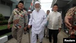 Abu Bakar Ba'asyir (tengah), tersangka dalang Bom Bali 2002 berjalan bersama Yusril Ihza Mahendra (kanan), penasihat pasangan capres-cawapres Joko Widodo-Ma'ruf Amin, di Lapas Gunung Sindur di Bogor, Indonesia, 18 Januari 2019.