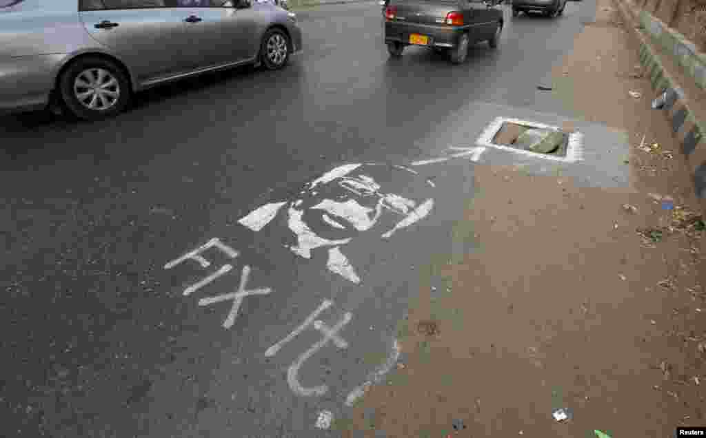 "Vehicles move past a graffiti, depicting the provincial chief executive with the message ""Fix It!"", near an uncovered drain hole along a road in Karachi, Pakistan. According to local media, a group of activists launched an idea to promote a campaign-project to draw the attention of authorities towards civic issues by art, by spray painting stenciled images of lawmakers with messages."