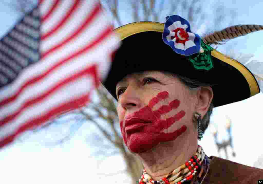 Bà Susan Clark ở Santa Monica, California, chống đối chương trình cải tổ bảo hiểm y tế, đứng trước Tối cao Pháp viện, ngày 28 tháng 3, 2012 giơ bàn tay sơn đỏ che ngang miệng để tỏ ý muốn nói rằng chủ nghĩa xã hội đang lấy mất quyền lợi và sự chọn lựa của