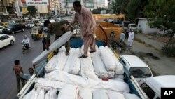 2013年9月28日,巴基斯坦志愿人员把帐篷和其它救灾物资装上卡车,送往俾路支省灾区。