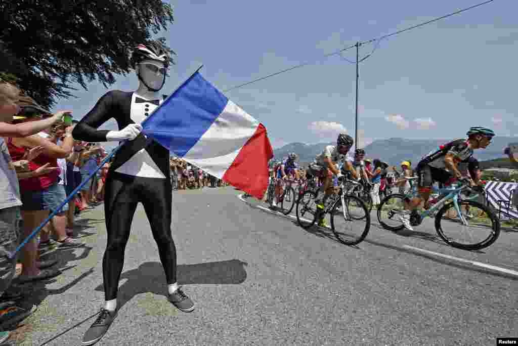 The pack of riders cycles past a French flag on Bastille day during the 242.5 km fifteenth stage of the centenary Tour de France cycling race from Givors to Mont Ventoux, July 14, 2013.