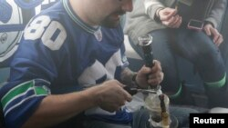 FILE - A man is seen smoking marijuana prior to last year's Super Bowl. A new study says college students are choosing marijuana over tobacco.