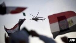 Một chiếc máy bay của quân đội Ai Cập bay qua trong lúc những người ủng hộ nhóm Huynh Đệ Hồi giáo đang biểu tình bên ngoài nhà thờ Hồi giáo Rabaa al-Adawiya ở Cairo, 5/7/2013. TOPSHOTS/AFP PHOTO/MAHMUD HAMS