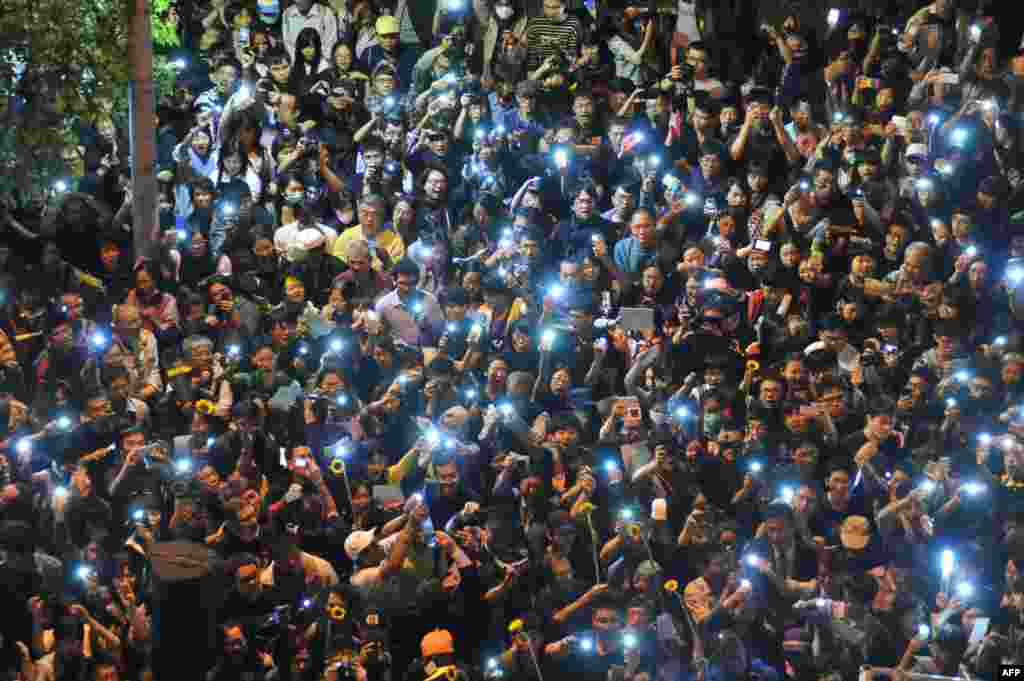 Protesters use their phones to show lights outside the parliament building in Taipei, Taiwan, after an occupy protest ended over a contentious trade pact with China.