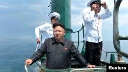 Chủ tịch Bắc Hàn Kim Jong Un đứng trên một chiếc tàu ngầm trong khi thị sát một đơn vị hải quân hôm 14/6/2014.