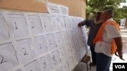 Quan chức hỗ trợ một cử tri tìm tên của mình trước khi biểu quyết trong một trường học ở Tripoli, ngày 25/6/2014.