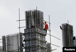 works at a construction site of an apartment complex in Colombo March 8, 2016. Sri Lankan Prime Minister Ranil Wickremesinghe, saying his country must break out of a debt trap, on Tuesday announced a rise in value added tax (VAT) and said the government will impose a capital gains tax.