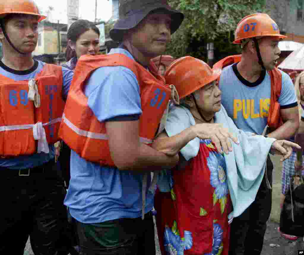 Philippine National Police officers help a resident to a waiting police truck as they enforce an evacuation following the swelling of Marikina River in Marikina city, east of Manila, August 20, 2013.