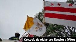 Un trabajador municipal coloca banderas del Vaticano, EE.UU. y el Distrito de Columbia en la avenida Pennsylvania por donde pasará la caravana papal.