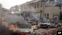 Sebuah mobil nampak terbakar di lokasi ledakan bom di gereja katolik St.Theresa di Madalla, dekat ibukota Abuja, Nigeria, menewaskan sedikitnya 27 orang pada perayaan Natal tahun lalu (Foto: dok). Serangan Malam Natal di Nigeria kembali terjadi tahun ini di luar kota Potiskum, negara bagian Yobe, meneewaskan sedikitnya eman orang.