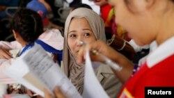 Seorang petugas sedang memeriksa dokumen seorang pekerja Filipina yang dipulangkan dari Kuwait di Bandara Internasional Ninoy Aquino di Paranaque, Metro Manila, Filipina, 12 Februari 2018.