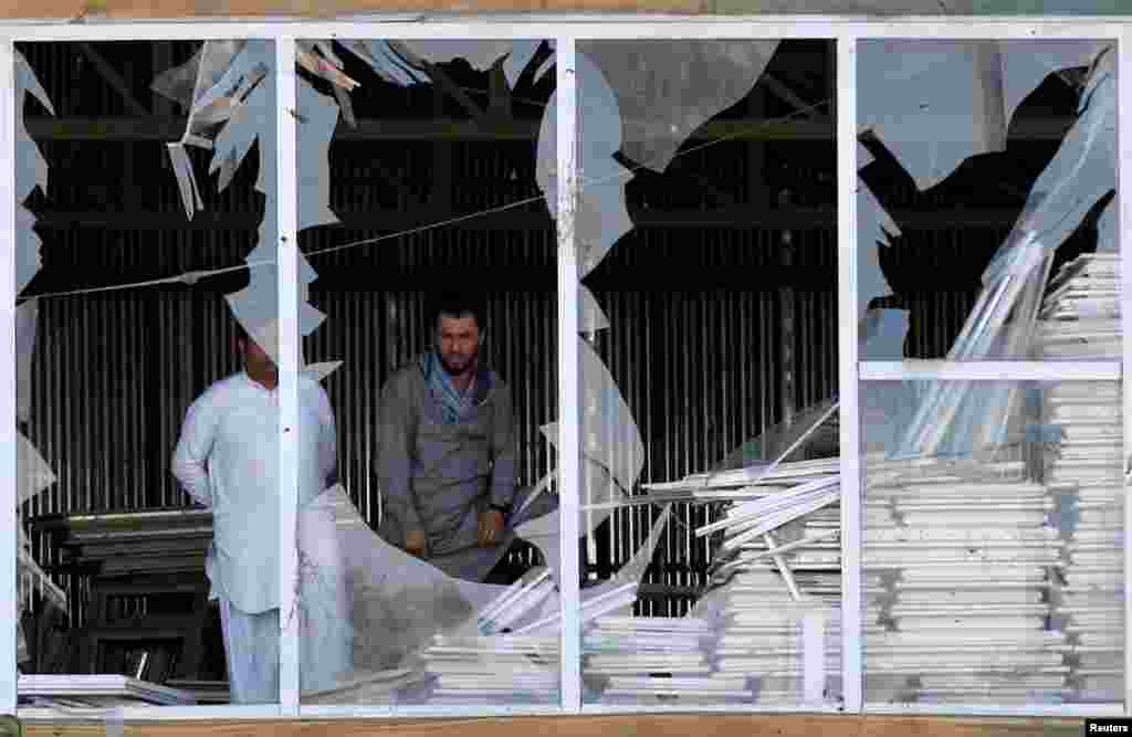 Afghan men look outside a broken window at the site of a suicide attack in Kabul, Afghanistan.