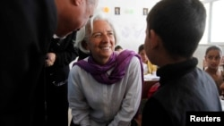 Christine Lagarde (C), International Monetary Fund Managing Director, speaks to a Syrian refugee student at Alimate school in Mafraq, Jordan, May 11, 2014.