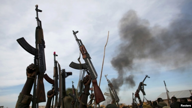 FILE - Rebel fighters hold up their rifles as they walk in front of a bushfire in a rebel-controlled territory in Upper Nile state, South Sudan, Feb. 13, 2014.