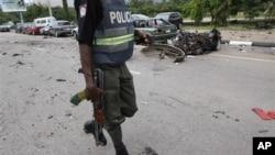 Un policier nigérian passant à côté de l'épave d'une voiture brûlée dans l'une des explosions d'Abuja