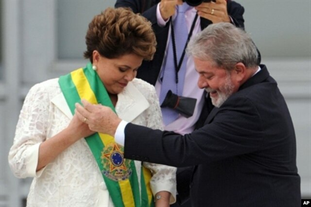 FILE - Newly sworn-in Brazilian President Dilma Rousseff receives the presidential sash from outgoing President Luiz Inacio Lula da Silva at the Planalto Palace in Brasilia, Jan. 1, 2011.
