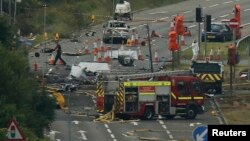 Emergency services personnel and crash investigators work at the site where a Hawker Hunter fighter jet crashed onto a road at Shoreham near Brighton, Britain Aug. 23, 2015.