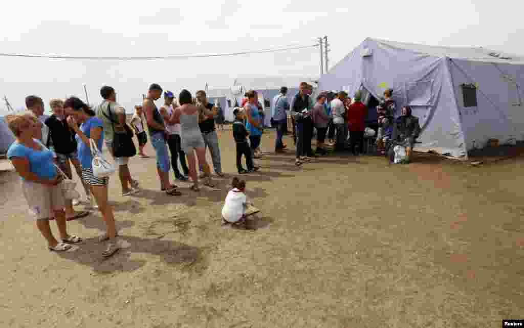 New arrivals stand in a line to register at a refugee camp in Russia's Rostov region, Aug. 18, 2014.