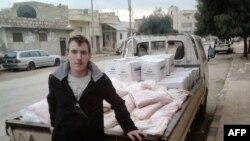 Nhân viên cứu trợ người Mỹ Abdul-Rahman (Peter) Kassig đứng cạnh một xe tải chở hàng cứu trợ. Anh Kassig bị bắt ở miền đông Syria hồi tháng 10 năm 2013 trong khi phân phát hàng cứu trợ cho một tổ chức từ thiện do anh thành lập.