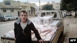 Foto sin fecha de Peter Kassig arrimado a un camión con provisiones en un lugar desconocido.