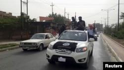 Pemberontak dari kelompok Negara Islam Irak dan Levant Muslim Sunni (ISIL) merayakan keberhasilan merebut kendaraan dari tentara Irak di Mosul (12/6).