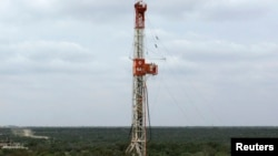 A rig contracted by Apache Corp drills a horizontal well in a search for oil and natural gas in the Wolfcamp shale located in the Permian Basin in West Texas, Oct. 29, 2013.