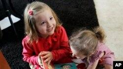 Coy Mathis (kiri) bermain dengan adiknya Auri di rumah mereka di Fountain, Colorado. Coy didiagnosa mengalami gangguan identitas gender dan merasa sebagai perempuan meski dilahirkan sebagai laki-laki. (AP/Brennan Linsley)