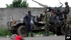 ພວກກໍາລັງທີ່ຈົງຮັກພັກດີຕໍ່ທ່ານ Alassane Ouattara ທີ່ ສປຊ ຮັບຮູ້ເປັນປະທານາທິບໍດີ Ivory Coast ພາກັນຖ້າຢູ່ທາງຫລັງ ຊາຍຄົນນຶ່ງ ທີ່ໄດ້ຮັບບາດເຈັບ ໃນນະຄອນ Abidjan, ວັນທິ 2, ເມສາ 2011.