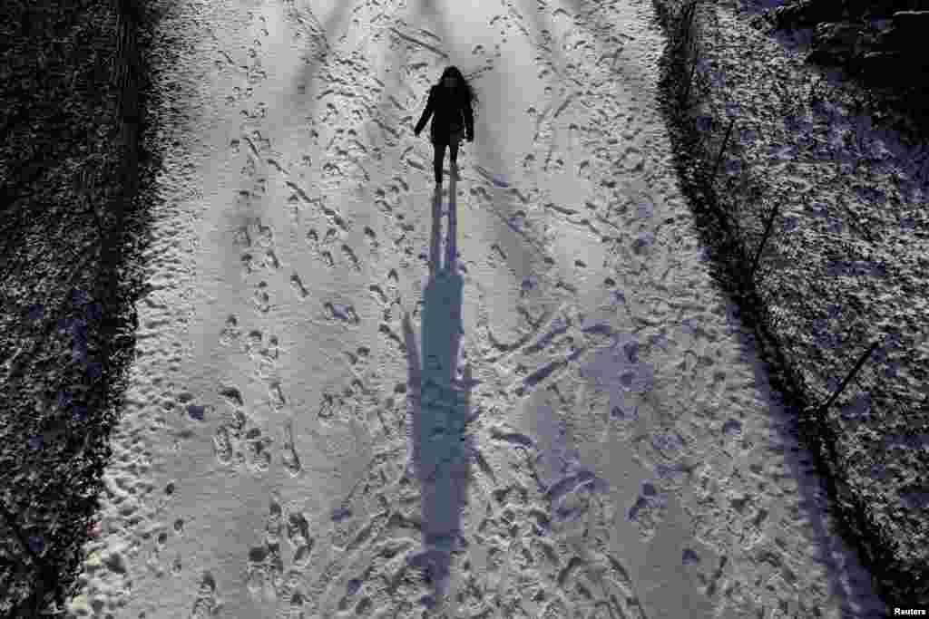 Seorang wanita berjalan di jalan yang tertutup salju di Central Park di New York.