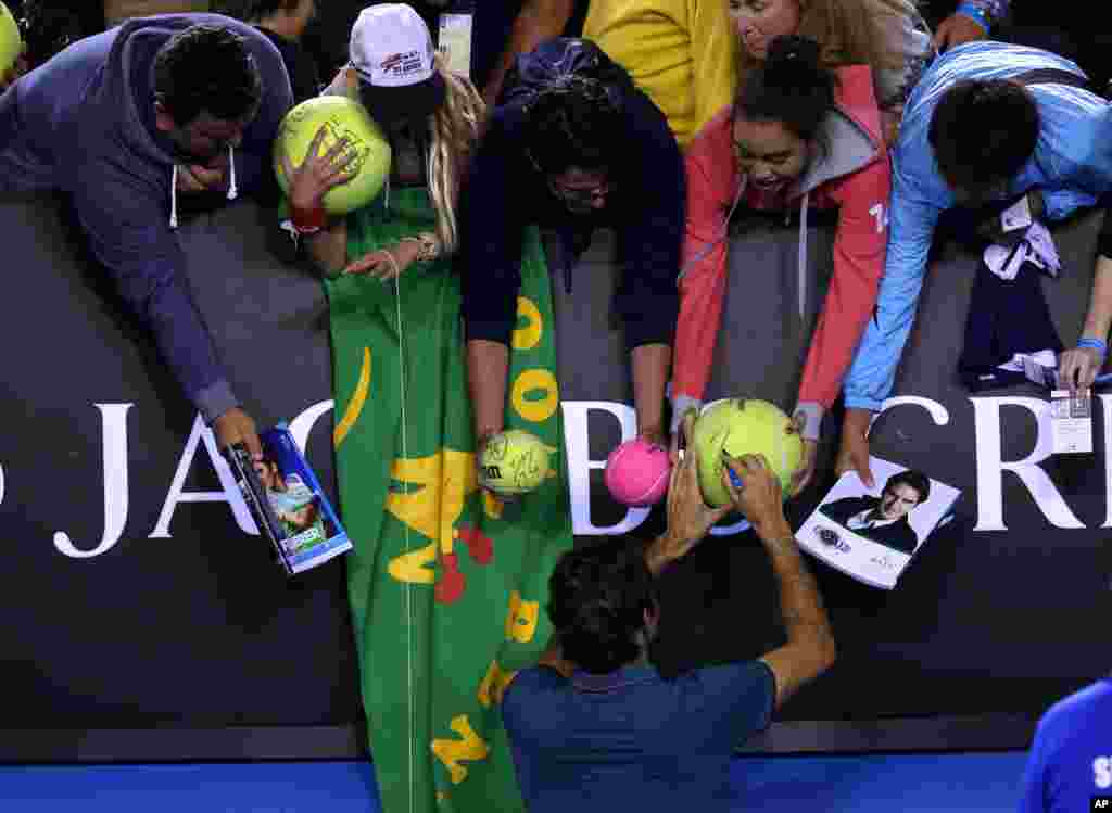 Roger Federer of Switzerland signs autographs for fans after defeating Andy Murray of Britain in the quarterfinal at the Australian Open tennis championship in Melbourne.