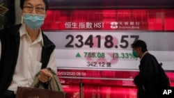 A man wearing a face mask walks past a bank's electronic board showing the Hong Kong share index at Hong Kong Stock Exchange Wednesday, March 25, 2020. Shares have advanced in Asia after the Dow Jones Industrial Average surged to its best day since 1933 a