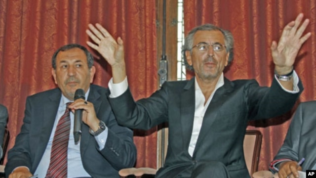 French philosopher Bernard-Henri Levy (R) and Suleiman Fortia, Misrata TNC member, speak during a news conference after lobbying French President Sarkozy for weapons supplies, in Paris, July 20, 2011