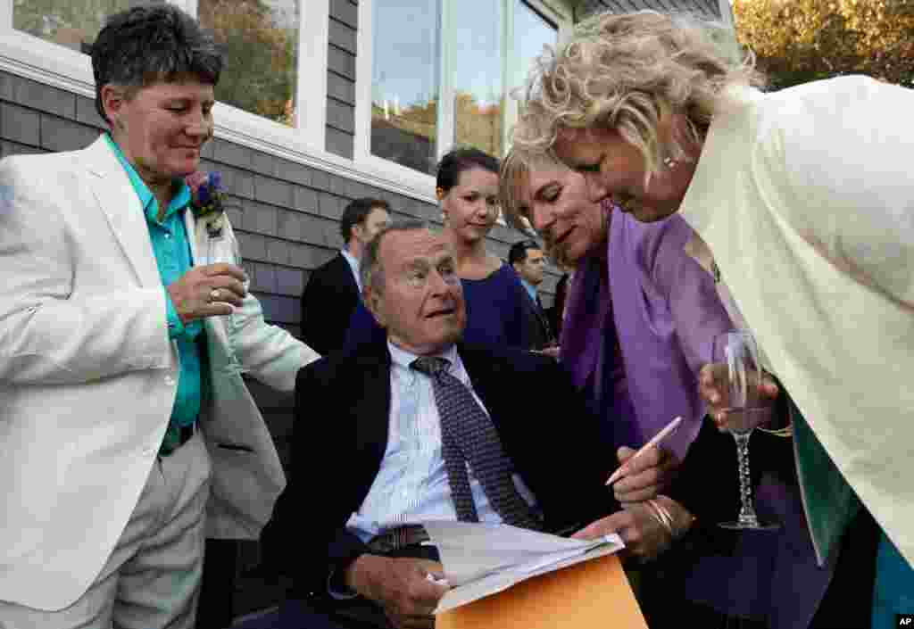 In this Sept. 21, 2013 photo, former president George H.W. Bush prepares to sign the marriage license of longtime friends Helen Thorgalsen (right) and Bonnie Clement (left) in Kennebunkport, Maine. Bush was an official witness at the same-sex wedding, his spokesman said, Sept. 25, 2013.